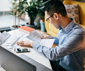 man at desk looking over paperwork
