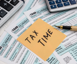 Tax forms with a sticky note saying tax time