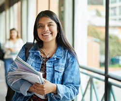 Student smiling in the hallway holding notebook